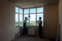 Two men doing internal works. Installing white plastic windows in a new multi-storey house. Development company staff royalty free stock images