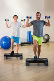 Two men doing step aerobic exercise with dumbbell on stepper Stock Photo