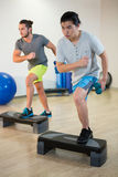 Two men doing step aerobic exercise with dumbbell on stepper Stock Photography