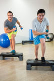 Two men doing step aerobic exercise with dumbbell on stepper Stock Images