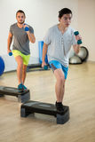 Two men doing step aerobic exercise with dumbbell on stepper Royalty Free Stock Images