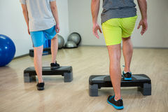 Two men doing step aerobic exercise with dumbbell on stepper Royalty Free Stock Photo
