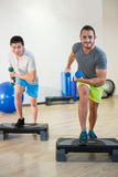 Two men doing step aerobic exercise with dumbbell on stepper Stock Image