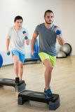 Two men doing step aerobic exercise with dumbbell on stepper Royalty Free Stock Image