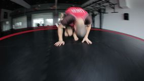 Two men doing synchrony somersault. In gym. Sportsmen warming up stock video footage