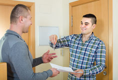 Two men at doorway with keys and contract Stock Image
