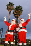 Two men dressed as Santa Clause under palm trees Royalty Free Stock Images