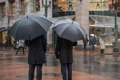 Two business men under umbrellas in the rain in an urban setting. Two men dressed in black professional clothing holding black umbrellas on a cold winter day in Royalty Free Stock Image
