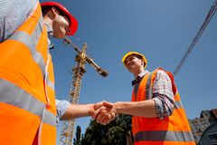 Two men dressed in orange work vests and helmets shake hands on the building site near the crane royalty free stock photos