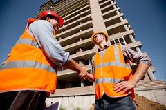 Two men dressed in shirts, orange work vests and helmets shake hands against the background of a multistorey building royalty free stock photo