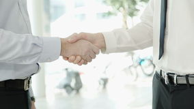 Two men dressed in a strict attire shaking hands with each other. Strong handshake takes place in amiable atmosphere. They met in sunny weather for the stock video footage