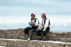 Two men dressed in traditional outfits specific for the Taquile Island region, one of them  knitting a hat Stock Photos