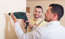 Two men with drill and level royalty free stock photos