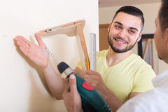 Two men with drill and level Royalty Free Stock Image