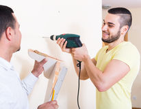 Two men with drill and level Stock Photography