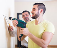 Two men with drill and level stock image