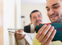 Two men with drill and level. Two positive skilled men with drill and level at home. Focus on drill royalty free stock images