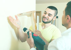 Two men with drill and level. Two smiling male adults with drill and level at home royalty free stock photos