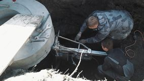 Two men drill circular hole in concrete manhole ring using industrial drill stock footage