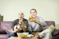 Two men drinking beer and watching soccer on tv. Two young men drinking beer at home and watching soccer on tv. Sport fans Royalty Free Stock Image