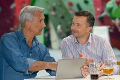 Two men with drinks looking at tablet stock photos