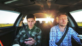 Two men driving in the car, drinking coffee, using phone, smiling. In full HD stock footage