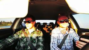 Two men driving in car having fun speaking stock video footage