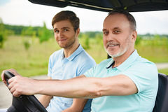 Two men driving cart on golf course. Golfing with my father. Close up of father and son enjoying day on golf course, driving cart Royalty Free Stock Photos