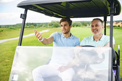 Two men driving cart on golf course Royalty Free Stock Image