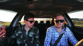 Two men, driving, discusing business issues in the car. In full HD stock footage
