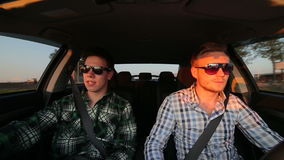 Two men driving fast in the car, speaking in sunglasses. In full HD stock video