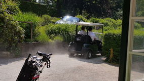 Two men driving by with a golf car. Two men driving down a sand path with a golf car. On the left side is a trolley full of equipment. On the right side are the stock video