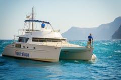 Two men driving motor yacht near coastline of Santorini island Royalty Free Stock Photo