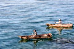Two men in dugout canoes on Lake Atitlan, Guatemala stock photo
