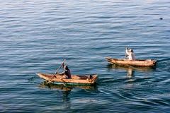 Two men in dugout canoes on Lake Atitlan, Guatemala stock photos