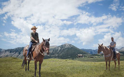 Two men each sitting on a horse with majestic mountains in the background. Horizontal image of a father and teenage son out horse back riding as they sit on royalty free stock photo
