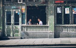 Two Men Eating While Facing Each Other Inside Store royalty free stock photography