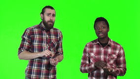 Two men eating french fries on green screen. Two multiracial men eating french fries, one a bearded Caucasian and the other a young black guy, upper body stock video footage