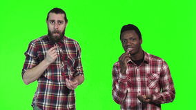 Two men eating french fries on green screen. Two multiracial men eating french fries, one a bearded Caucasian and the other a young black guy, upper body stock footage
