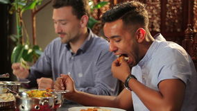 Two men eating a pitta in the indian restaurant. The man try the pitta with some ingredients. The swarthy guy ask the man about dish. The men smiles and enjoy stock footage