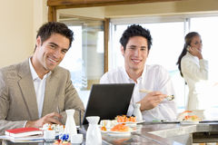 Two men eating in sushi bar, smiling, portrait Royalty Free Stock Images