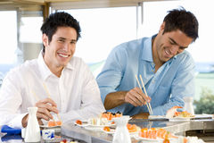 Two men eating in sushi bar, smiling, portrait Royalty Free Stock Photo