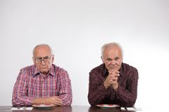 Two men with empty plates stock photography