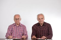 Two men with empty plates stock image