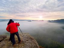 Photographying in wild nature. Nature photographer with big camera on tripod stay on summit rock. Listen to muse. Two men enjoy photographying in wild nature Stock Image