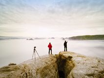 Photographying in wild nature. Nature photographer with big camera on tripod stay on summit rock. Listen to muse. Two men enjoy photographying in wild nature Royalty Free Stock Photo