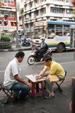Two men enjoy playing checkers with bottle caps sitting on a noisy street in Bangkok during the day. stock image