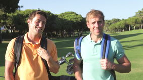 Two Men Enjoying Game Of Golf. Two men carrying golf clubs walk along fairway towards camera talking.Shot on Canon 5d Mk2 with a frame rate of 30fps stock video