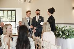 Two Men Exchanging Vows On Their Wedding Day. Two men are exchanging vows on their wedding day Royalty Free Stock Photography