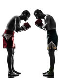 Two men exercising thai boxing salute  silhouette. Two caucasian  men exercising thai boxing saluting in silhouette studio  on white background Royalty Free Stock Images